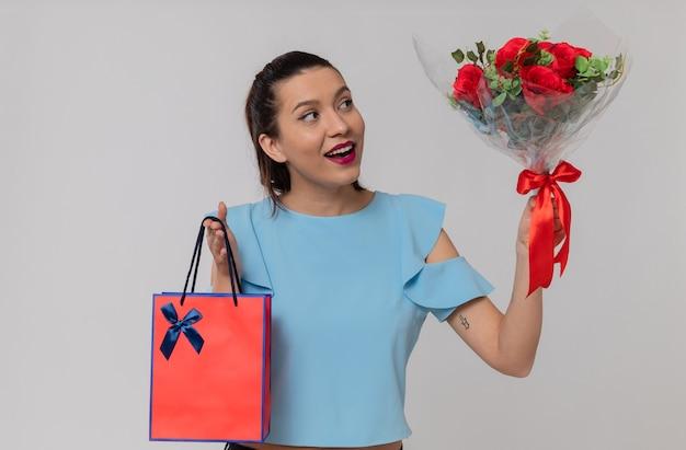 Jolie jeune femme impressionnée tenant un sac-cadeau et regardant un bouquet de fleurs