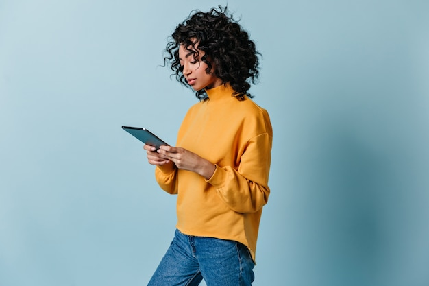 Jolie jeune femme en jeans à l'aide de tablette numérique