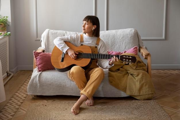 Jolie jeune femme jouant de la guitare à l'intérieur