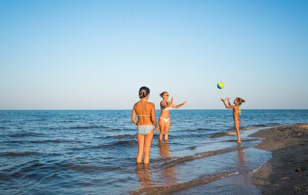 Jolie jeune femme joue au ballon avec ses charmantes filles en nageant dans la mer par une chaude journée d'été ensoleillée. concept de vacances avec des enfants. espace publicitaire