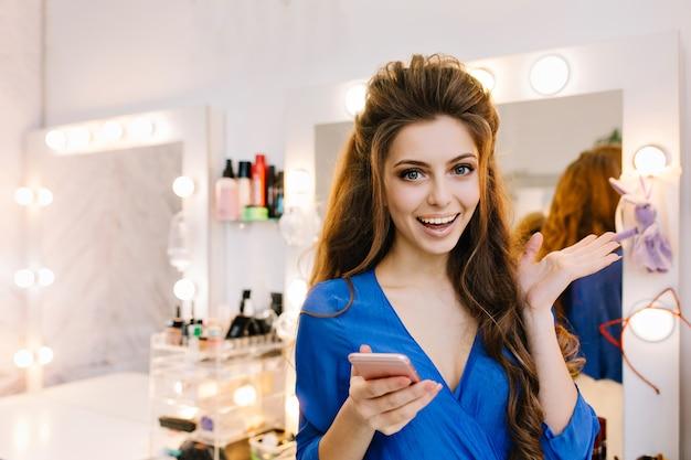 Jolie jeune femme joyeuse excitée en chemise bleue avec de longs cheveux brune exprimant des émotions positives à la caméra dans un salon de beauté