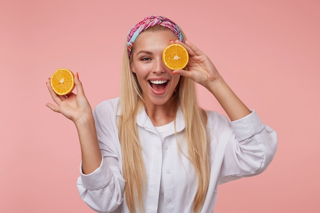 Jolie jeune femme avec un large sourire charmant se moquant, tenant la coupe orange près de son œil