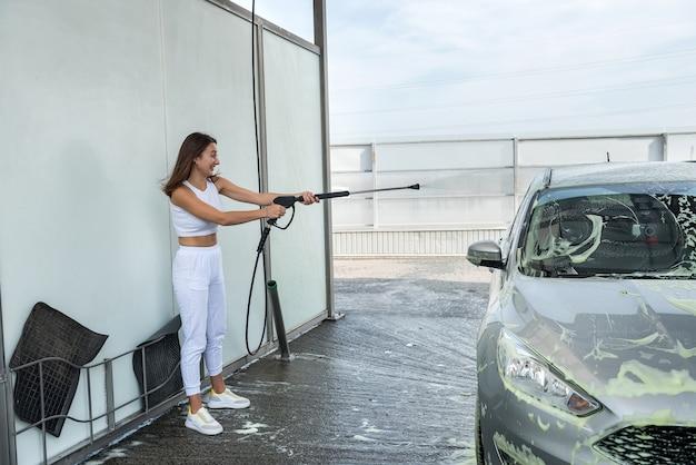 Jolie jeune femme lave sa voiture en station de lavage de voiture