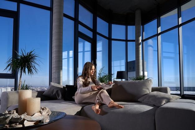 Jolie jeune femme lisant un livre sur le canapé