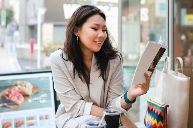 Jolie jeune femme lisant un magazine