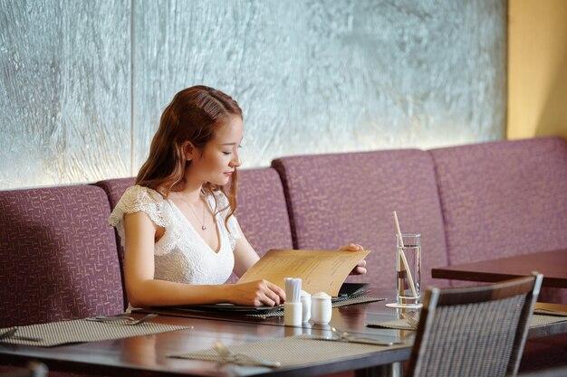 Jolie jeune femme lisant le menu à la table du restaurant en attendant un rendez-vous ou un ami