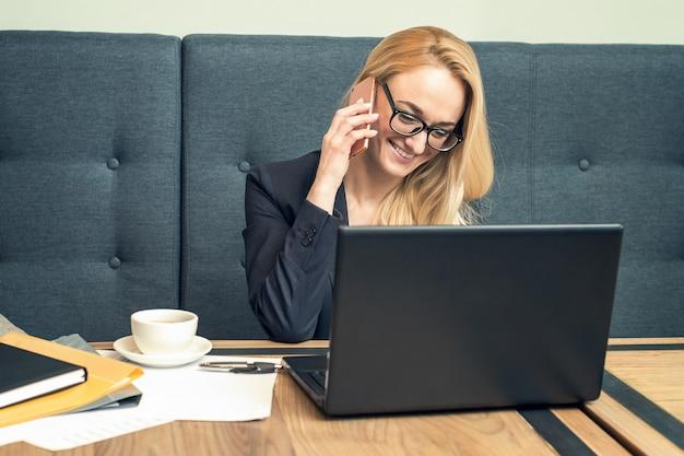 Jolie jeune femme à lunettes parle au téléphone au bureau avec un client.