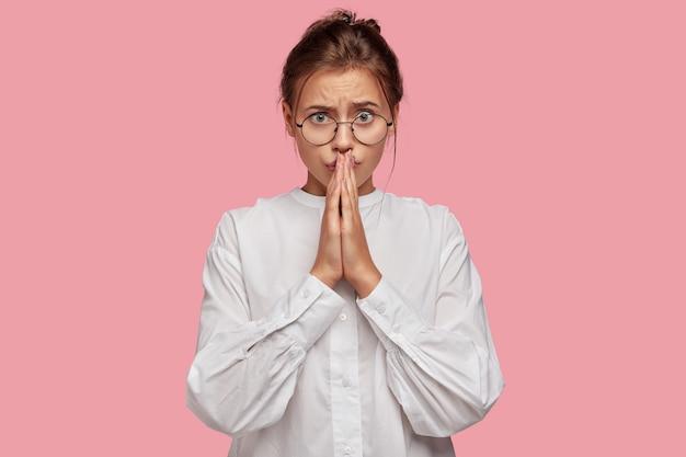 Jolie jeune femme avec des lunettes posant contre le mur rose