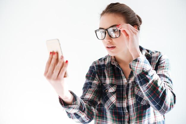 Jolie jeune femme à lunettes tenant et utilisant un téléphone portable