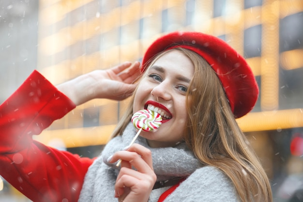 Jolie jeune femme en manteau rouge mordant des bonbons sucrés pendant les chutes de neige. espace libre