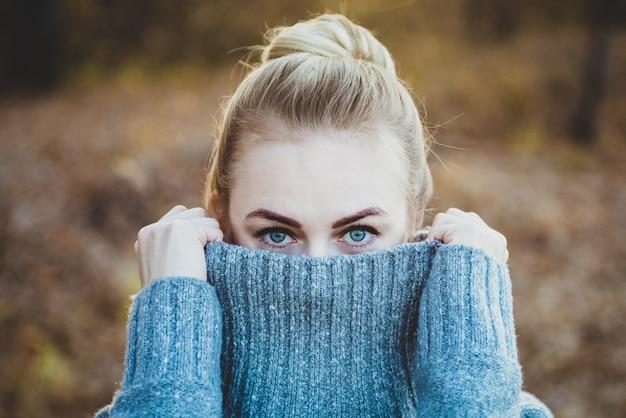 Jolie jeune femme avec un maquillage naturel avec de beaux yeux bleus ferme les lèvres avec un pull à l'extérieur