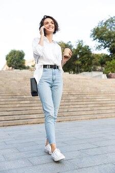 Jolie jeune femme marchant en bas dans la rue