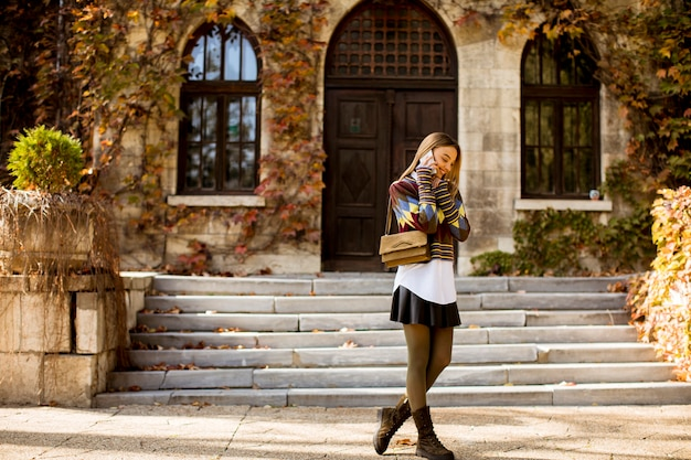 Jolie jeune femme marchant dans le parc en automne
