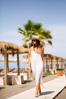 Jolie jeune femme marchant sur une plage en été
