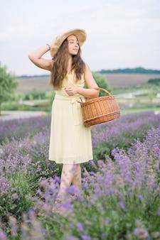 Jolie jeune femme, marchant avec un sac en osier dans un champ de lavande en fleurs d'été
