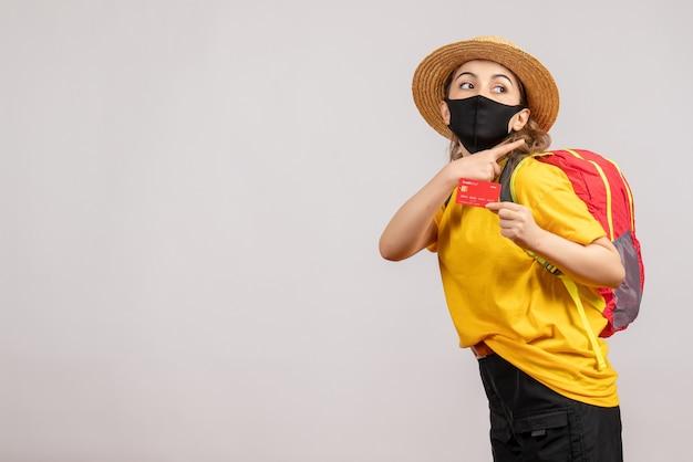 Jolie jeune femme avec un masque noir tenant une carte de crédit sur blanc