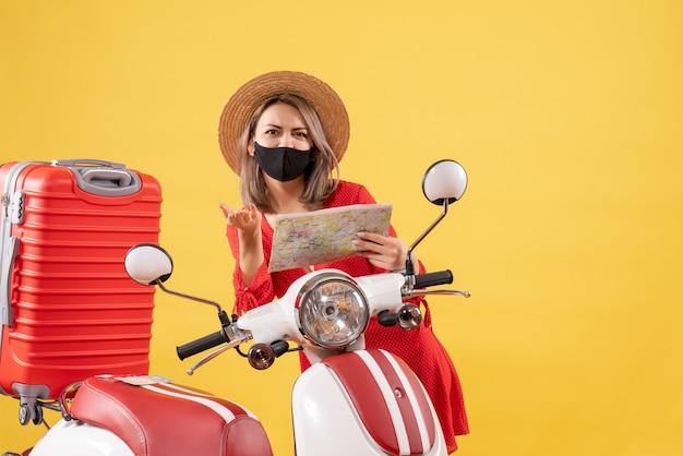 Jolie jeune femme avec un masque noir tenant une carte près d'un cyclomoteur