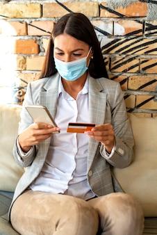 Jolie jeune femme avec un masque protecteur à l'aide de téléphone mobile carte de crédit anc dans le café