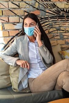 Jolie jeune femme avec un masque de protection à l'aide de téléphone portable dans le café