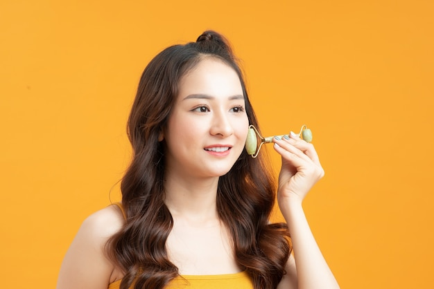 Jolie jeune femme massant le visage avec un rouleau de jade isolé sur beige