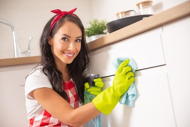 Jolie jeune femme de ménage avec un ruban rouge dans les cheveux et un tablier nettoyant la porte blanche de l'armoire de cuisine avec un chiffon et un détergent dans des gants en caoutchouc jaune.