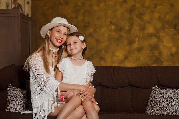 Jolie jeune femme mère avec une fillette de quatre ans à l'intérieur de la pièce. famille heureuse sur le canapé à la maison