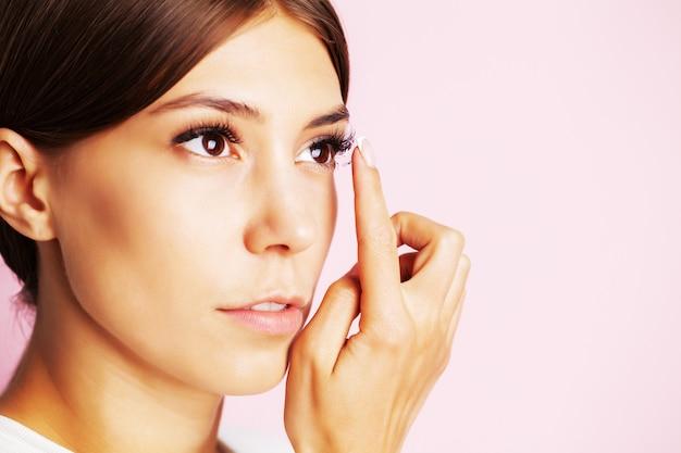 Jolie jeune femme met des lentilles de contact pour la vue