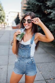 Jolie jeune femme mince souriante à lunettes de soleil et chemise dans la ville