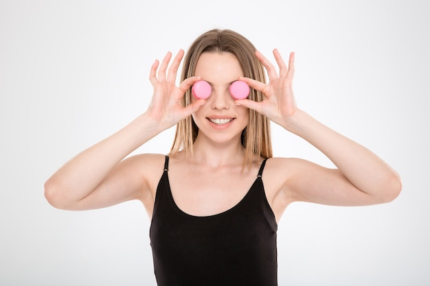 La jolie jeune femme a mis des macarons au lieu des yeux