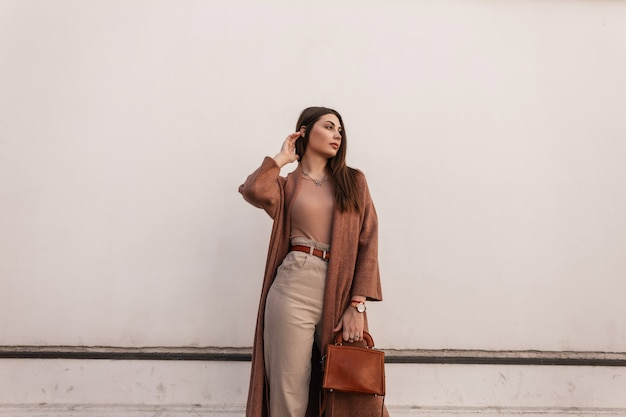Jolie jeune femme à la mode en manteau élégant en pantalon avec sac à main marron élégant en cuir posant près d'un bâtiment blanc vintage dans la rue. une jolie fille urbaine se repose à l'extérieur. tenue tendance décontractée de printemps