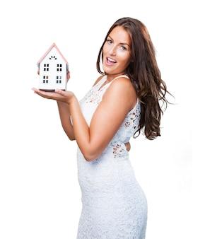 Jolie jeune femme montrant un objet de la maison
