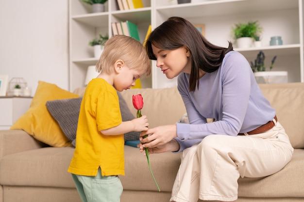 Jolie jeune femme montrant la tulipe rouge à son mignon petit fils alors qu'il était assis sur un canapé en face de lui et parle de la fleur