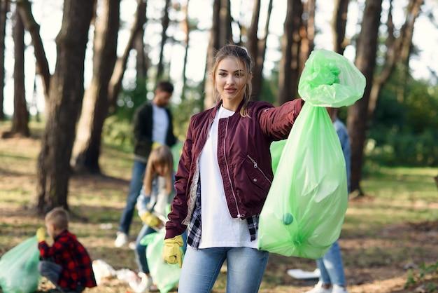 Jolie jeune femme montre un paquet de déchets complet en arrière-plan de ses amis bénévoles ramassant des déchets au parc.