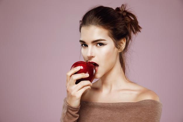 Jolie jeune femme mordant une pomme rouge sur rose