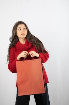 Une jolie jeune femme sur un mur blanc tenant des sacs à provisions