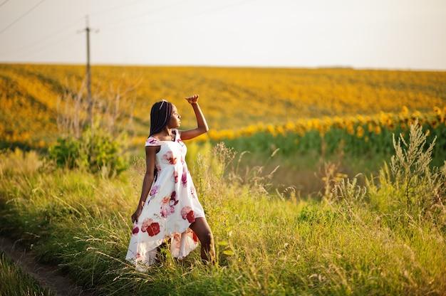 Jolie jeune femme noire vêtue d'une robe d'été pose dans un champ de tournesol.