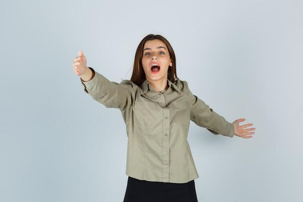 Jolie jeune femme ouvrant les bras pour un câlin en chemise, jupe et se demandant. vue de face.