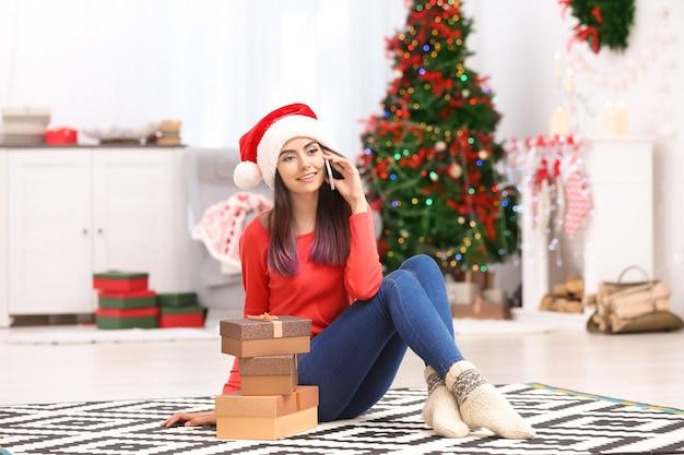 Jolie jeune femme parlant au téléphone portable à la maison