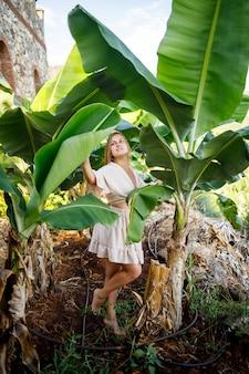 Jolie jeune femme à la peau claire se tient près des bananiers dans un parc tropical. mise au point sélective
