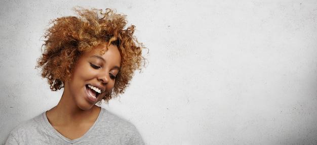 Jolie jeune femme à la peau foncée avec une coupe de cheveux élégante et un chant perçant du visage, ouvrant largement la bouche, regardant vers le bas avec un sourire joyeux et heureux.