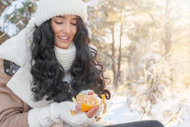 Jolie jeune femme pèle la mandarine dans la forêt de fées d'hiver, concept de vacances de noël ou du nouvel an