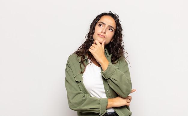 Jolie jeune femme pensant, doutant et confuse, avec différentes options, se demandant quelle décision prendre