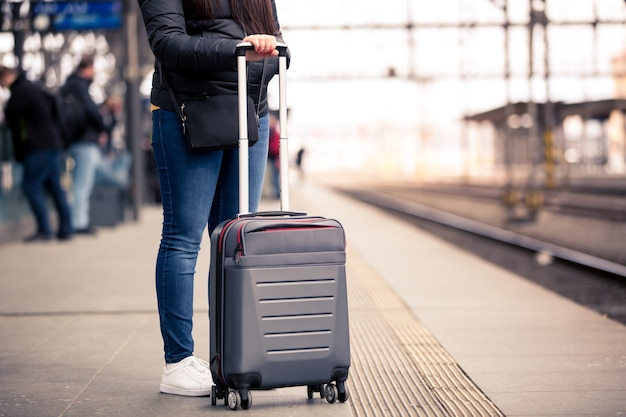 Jolie jeune femme avec petit bagage à main en attente à la gare de traint pour son train, concept de transport