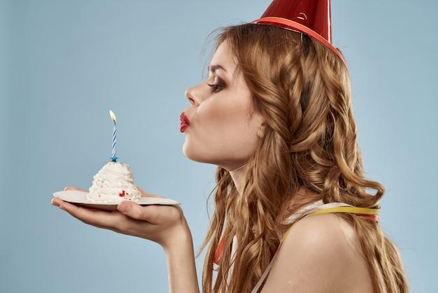 Jolie jeune femme avec un petit gâteau et des bougies fête son anniversaire