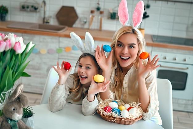 Jolie jeune femme avec une petite fille mignonne se préparent pour la célébration de pâques. maman et sa fille portant des oreilles de lapin passent du temps ensemble avant pâques en peignant des œufs.