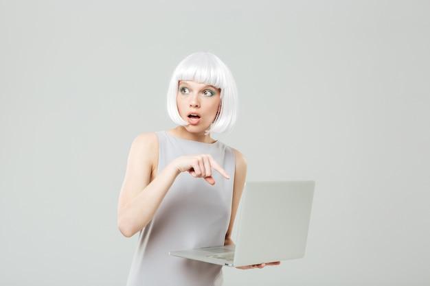 Jolie jeune femme peu confiante tenant et utilisant un ordinateur portable