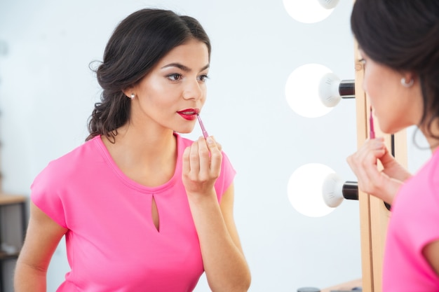Jolie jeune femme avec un pinceau à lèvres regardant le miroir et appliquant du rouge à lèvres rouge sur ses lèvres