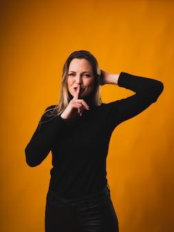 Jolie jeune femme plaçant une de ses mains derrière sa tête et avec l'autre, elle place un doigt dans sa bouche simulant le silence portant une chemise et un pantalon noirs