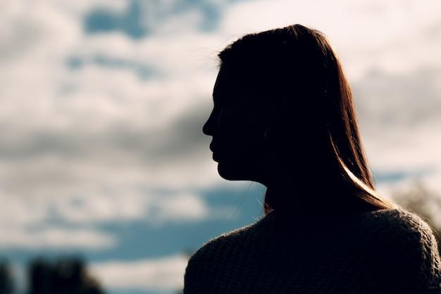 Jolie jeune femme en plein air dans le parc en été. portrait de silhouette avec ciel.