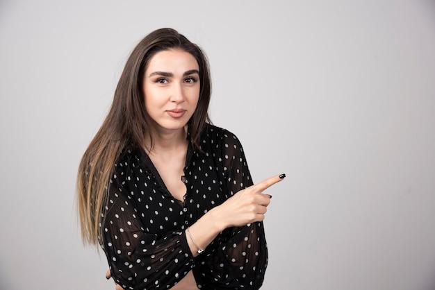Jolie jeune femme pointant un doigt sur un mur gris.